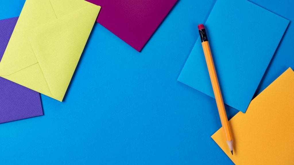 Blue, yellow, orange, and purple envelopes and a pencil sitting on a blue background