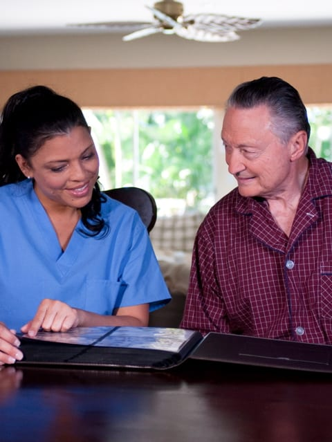 Nurse and senior man flipping through a photo album | Credit: ARARF