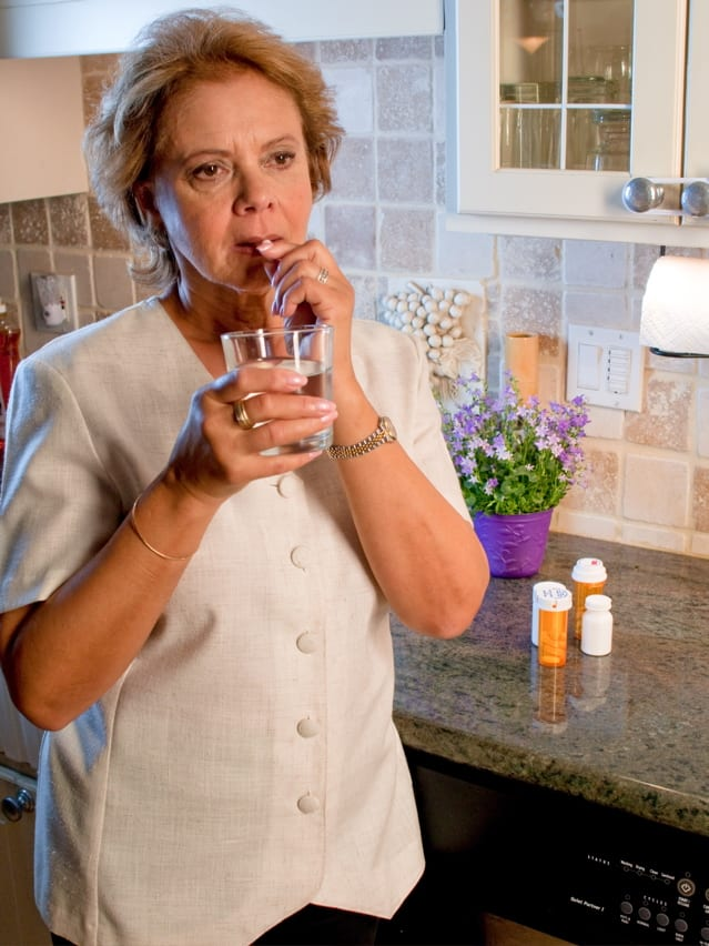 woman taking a sip of water with medication behind her