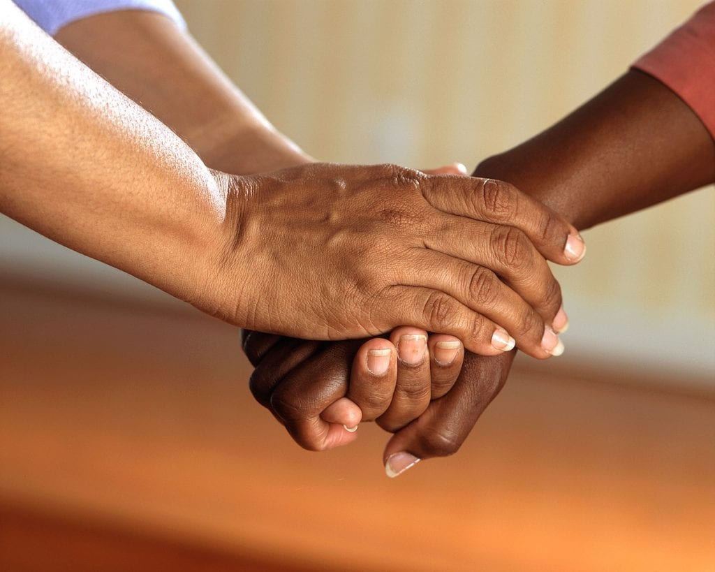 One person holds another persons hands