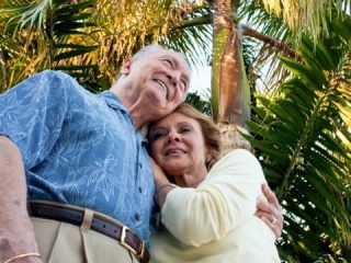 A senior man and woman smile and hug under palm trees | Credit: ARARF